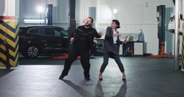 Nejlepší tým na auto servis centrum kancelář pracovník žena a mechanik muž tanec uprostřed garáže legrační a vzrušený