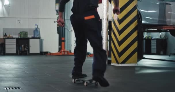 On a skateboard mechanic guy in a uniform have a fun time at his work place in a modern auto service center