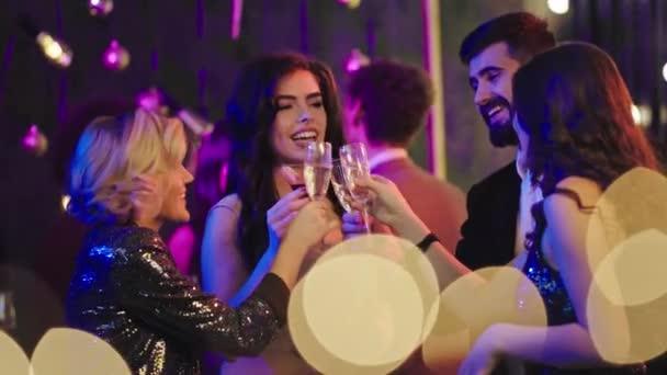 Gute Stimmung bei der Partygruppe junger Leute mit lächelnden Gesichtern, die die Nacht genießen, mit Sektgläsern jubeln und aufgeregt sind