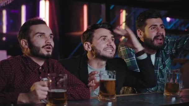 In a pub group of guys very attractive closeup to the camera meeting all together to watch a TV game match they are nervous and concentrated looking at the game