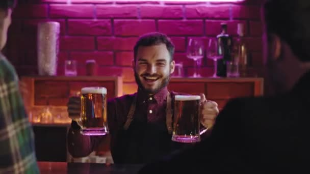 Happy and good looking bartender in a modern pub giving to big glasses of beer to his cu on a bar table