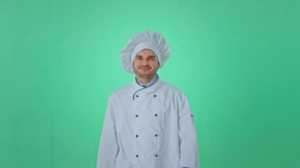 Baker fiatal férfi egyenruhában egyenesen a kamera elé sétál, pózol és mosolyog karizmatikusan egy zöld stúdióban.
