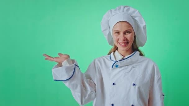 Pohledná žena pekař v zelené zdi studia dívá přímo do kamery s úsměvem velké a zvednout ruku a udržet hrát, jako by s něčím v ní