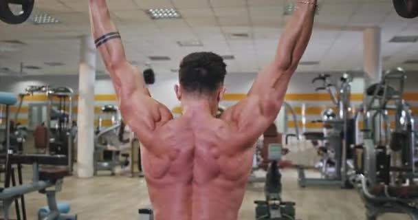 Bere video ze zadní části kulturistiky muž dělá cvičení pro jeho záda získat více svalů v moderní tělocvičně třídy
