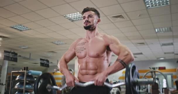 V moderní tělocvičně před kamerou atletický chlap dělá cvičení na jeho biceps a triceps má pot tělo, fit cross concept