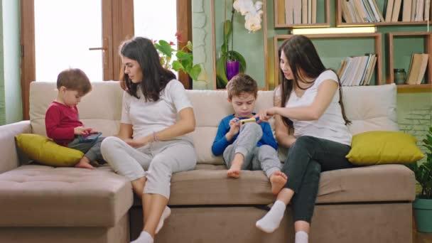 V obývacím pokoji na pohovce dvě atraktivní mladé matky se svými dětmi tráví čas spolu, zatímco kluci pomocí smartphonu hrát nějaké hry
