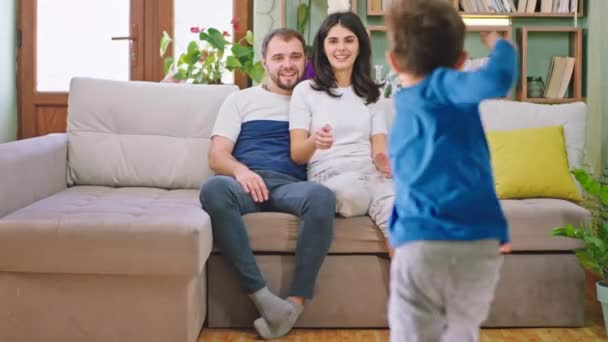 Two kids have a fun time with their young parents while sitting on the sofa the kids running to the parents they hugging each other and enjoying the time in the family. Shot on ARRI Alexa Mini