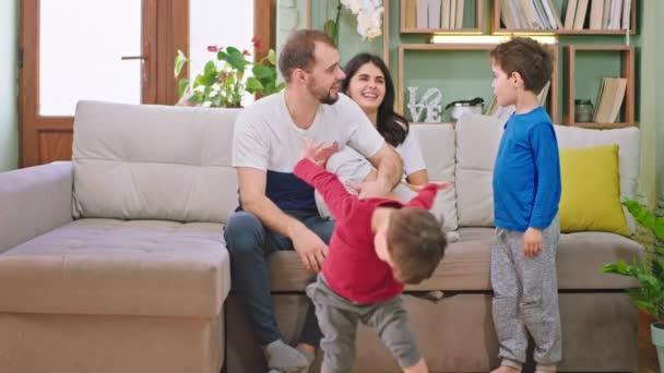 Mosolygó nagy és boldog fiatal család két gyerekkel és vonzó szülők élvezik az időt otthon a kanapén játszanak, és jól érzik magukat
