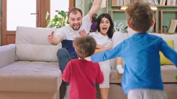 Pár klábosení na pohovce jejich dvě děti běží k nim a sedí na pohovce všichni společně hrát a usmívat se velké rychlosti zábavy. Shot na ARRI Alexa Mini