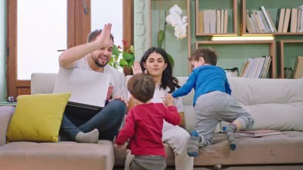 Mladá atraktivní rodina se dvěma dětmi v obývacím pokoji sedí na pohovce, usmívají se a hrají si spolu a skvěle se baví. Shot na ARRI Alexa Mini
