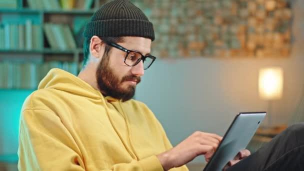 V kanceláři se usmívá velký dělník mladý muž psaní něco na tablet pak se dívá přímo do kamery