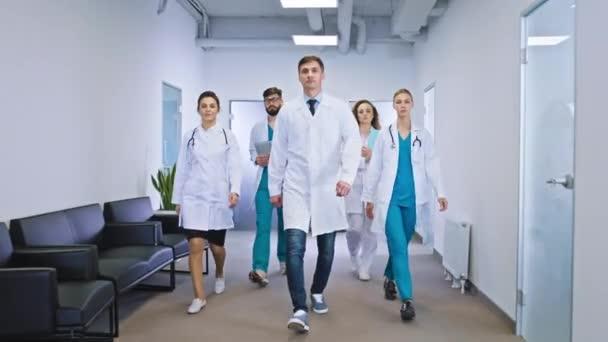 Großes Team von Ärzten und Krankenschwestern multiethnisch auf dem Krankenhausflur, direkt vor der Kamera