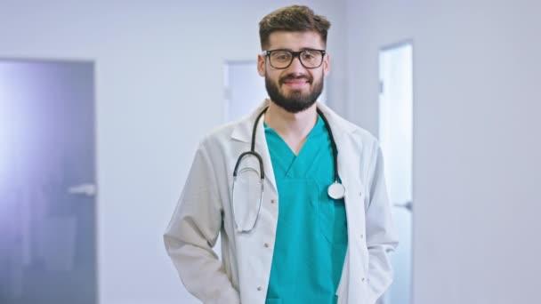 Portrét mladého lékaře na chodbě nemocnice, jak se dívá přímo do kamery a usmívá se.