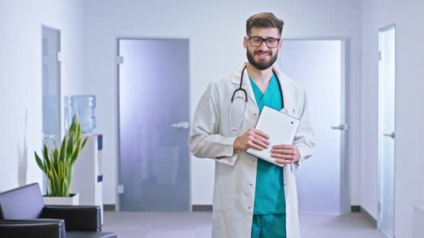 Dobře vypadající lékař stojí před kamerou v moderní nemocniční chodbě drží svůj elektronický tablet a usmívá se