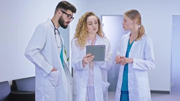 Konzentriert diskutierten Hauptärztin und Krankenschwestern auf dem modernen Krankenhausflur das Problem der Patientin mit dem digitalen Tablet. Schuss auf ARRI Alexa Mini