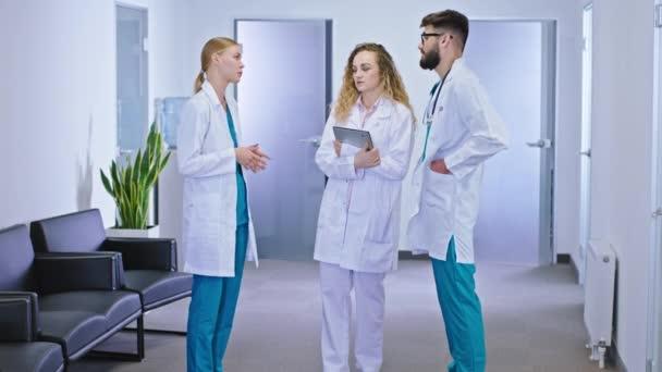 Mitten auf dem Flur in der Krankenhausgruppe analysieren und diskutieren Ärzte die zukünftige Behandlung eines Patienten aus dem Krankenhaus. Schuss auf ARRI Alexa Mini