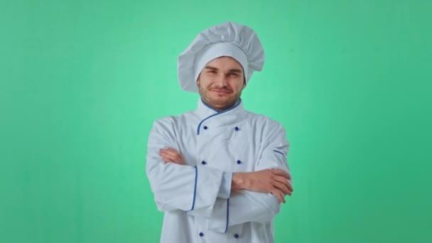 Atraktivní pekař pózuje před kamerou, zkříží ruce v zeleném studiu a má široký úsměv.