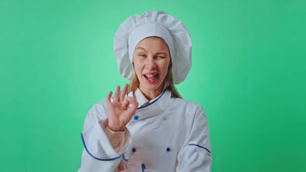 Nagyon vonzó és vicces pék nő előtt a kamera a háttérben zöld fal, hogy vicces arc ő gesztikuláló kézzel mutatják rendben