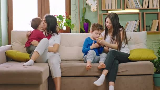 At Home in the living room two mothers with their kids spending the time while chatting and the kids using the smartphones to play the games. Shot on ARRI Alexa Mini
