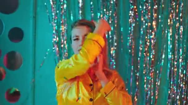 Táncoló karizmatikus szőke hajú hölgy egyenesen a kamerába néz, és élvezi az időt egyedül. 4k