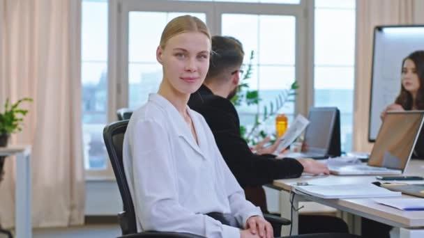 Atraktivní žena s velkým úsměvem kancelářské jesle na tréninkovém semináři si pauzu dívá přímo do kamery a usmívá se velké