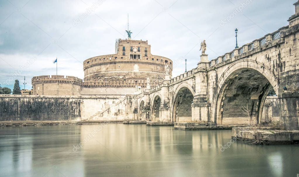 Фотообои Ponte Sant'Angelo bridge crossing the river Tiber and Castel Sant'Angelo (AD 135), mausoleum of Hadrian, now a museum and art gallery illuminated at night in the heart of Rome.