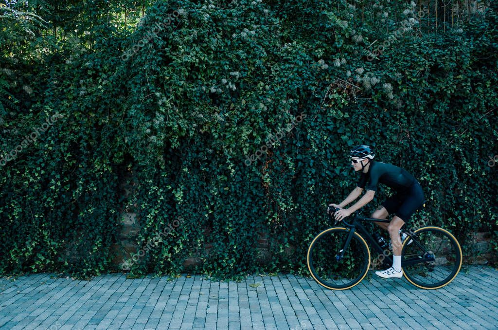 male cyclist in front of bush leaves