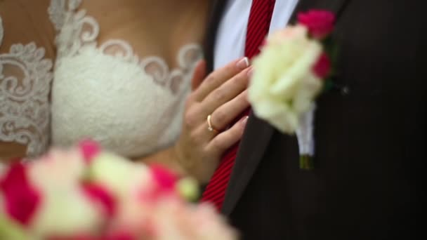 bride hugs groom holding hand with bouquet of peonies before grooms chest