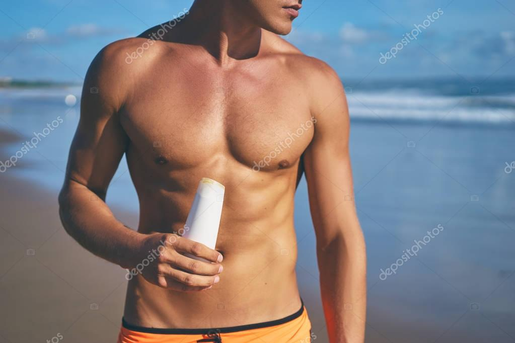 Man holding sunscreen lotion