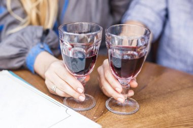 man and woman holding glasses of red wine on wooden background