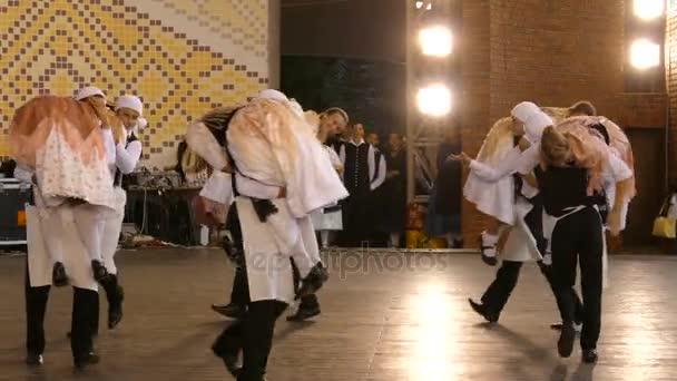 Mladý německý tanečníků v tradičních lidových krojích provést jednu legrační lidový tanec