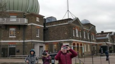 LONDON, ENGLAND - NOVEMBER 29, 2017: Panoramic view with people that visit Royal Greenwich Observatory at Greenwich Hill, skyline of Canary Wharf and Queen's House.