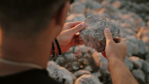 Muž, který držel kámen v jeho rukou closeup