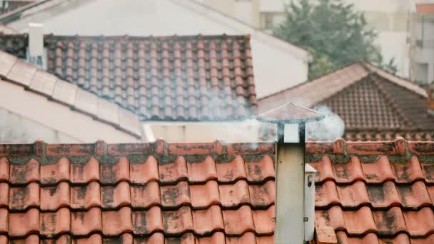 Kouř vychází z komína domu. Potrubí na střeše. Komín. Venkovský dům. Dům s komínem. Kouř na pozadí střechy