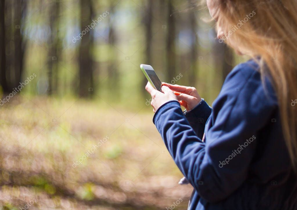 Woman using mobile phone during walk in park
