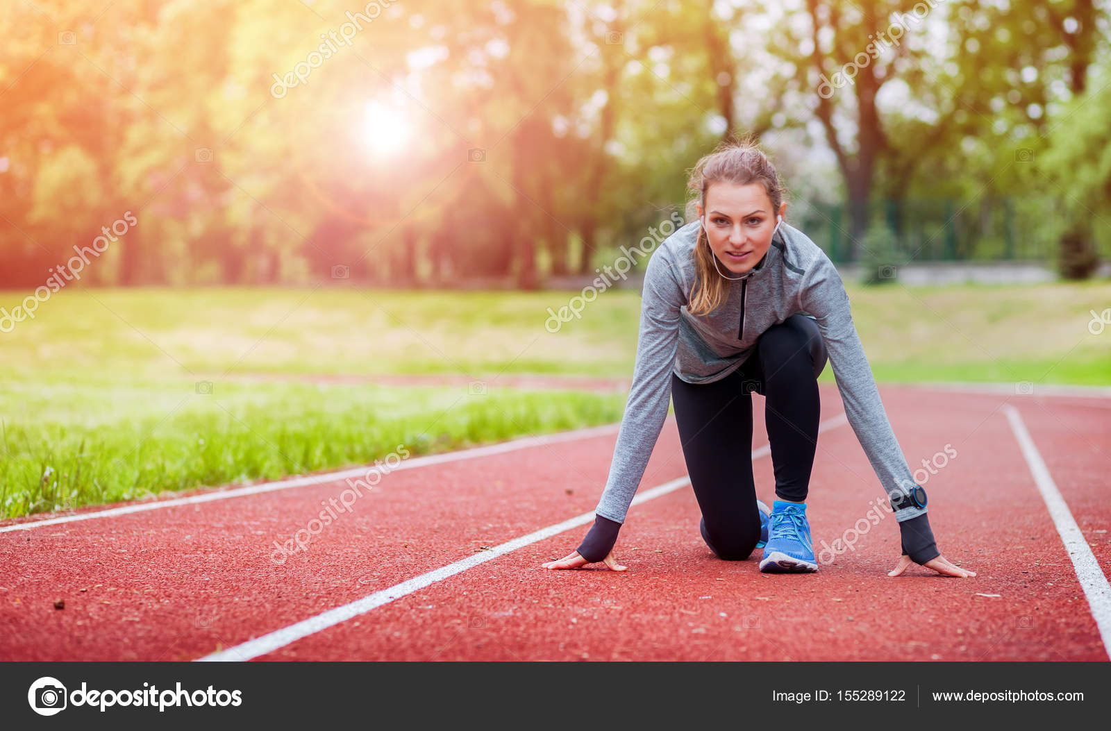 Athletic Woman On Running Track Getting Ready To Start Run Photo By Leszekglasner