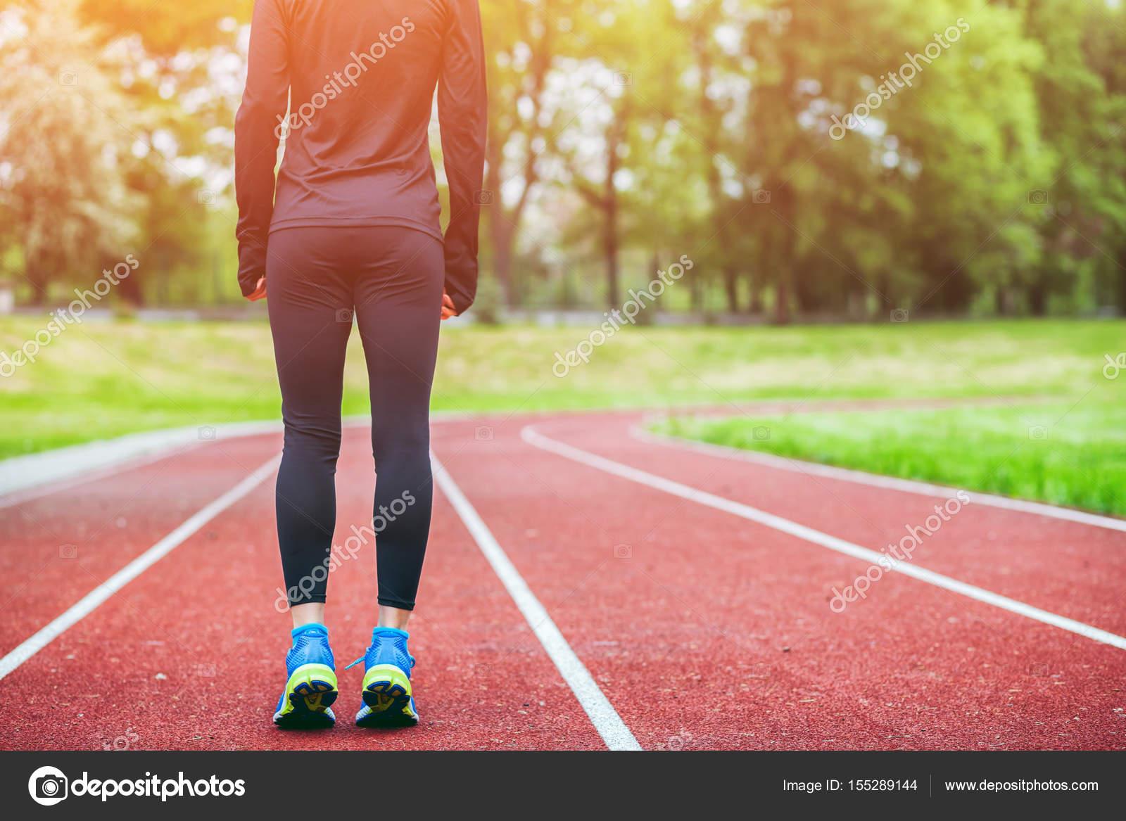 11722ac1c6d Atletisk kvinna på löparbana redo att börja springa tillbaka Visa– stockbild