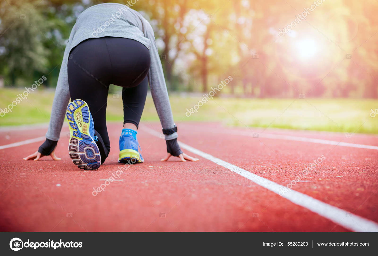 Athletic Woman On Running Track Getting Ready To Start Run Back View Stock Photo