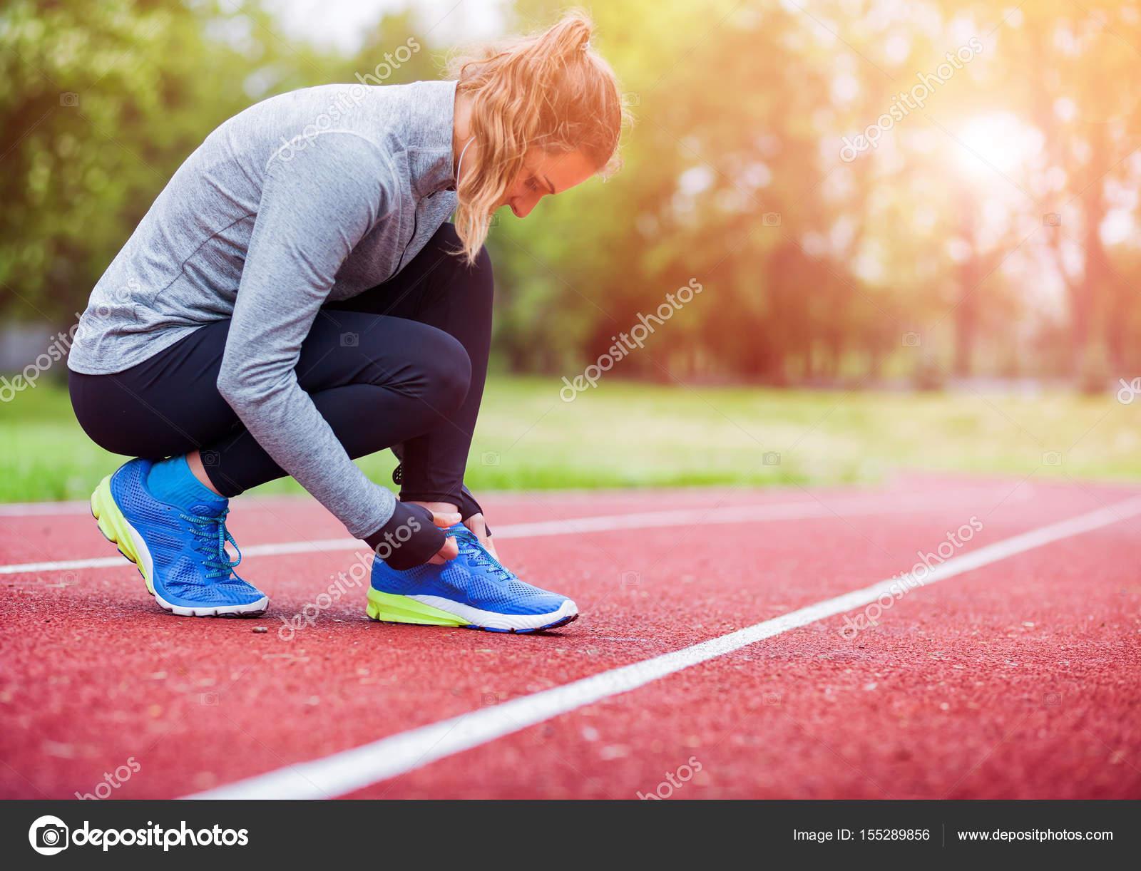 nouveau sommet bonne réputation vente officielle Femme athlétique sur piste d'athlétisme de lier les lacets ...