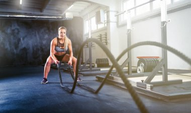 Fitness woman working out with battle rope, crossfit training