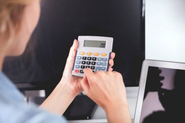 Woman at home office using calculator, calculating budget