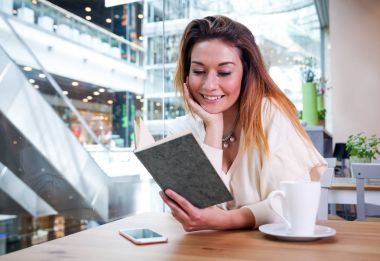 Relaxed smiling girl reading book in cafe at shopping mall
