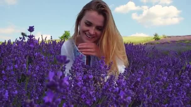Young blonde woman in lavender field in summer day