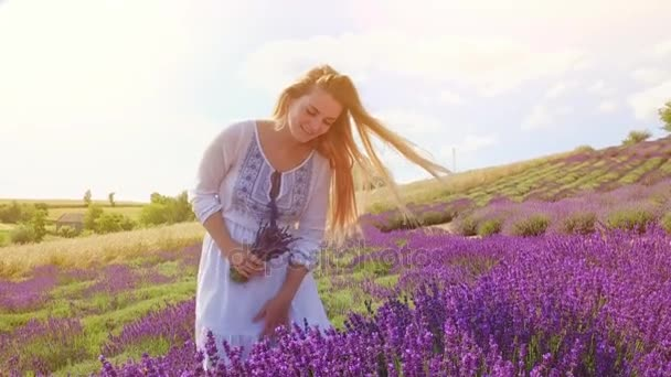Mladá žena s kyticí čerstvého levandule v levandulové pole
