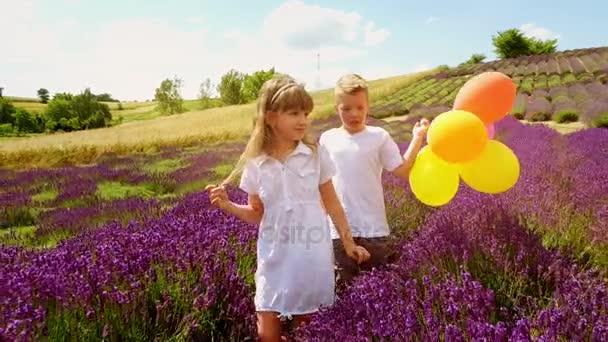 Fiú és a lány fut a levendula mező színes léggömbök