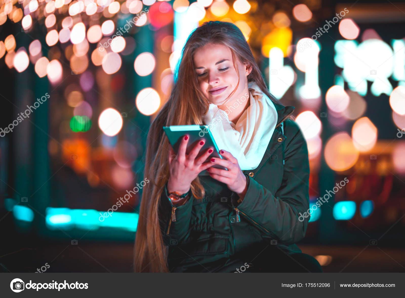 fille dans la ville pendant la nuit l aide de tablette assis sur un banc photographie. Black Bedroom Furniture Sets. Home Design Ideas