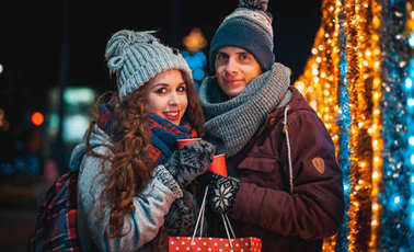 Cheerful couple with hot drinks on Christmas lights background during evening walking in the city