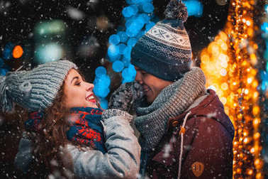 Loving couple on Christmas lights background during evening walking in the city with snowfall
