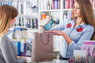 Saleswoman at beauty store putting cosmetics into shopping bag for customer