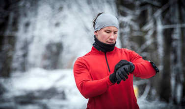 Runner wearing warm clothes looking at sport watch during winter training